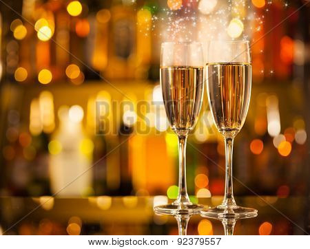 Celebration theme with two glasses of champagne. Blur bottles on background