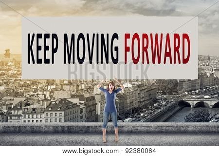 Keep moving forward, words on blank board hold by a young girl in the outdoor.