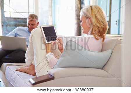 Mature Couple At Home In Lounge Using Digital Devices
