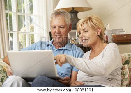 Mature Couple Sitting On Sofa At Home Using Laptop