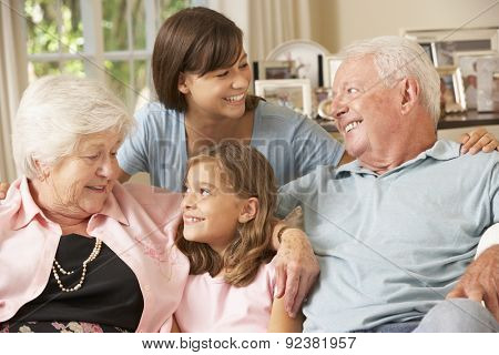 Grandparents Sitting On Sofa With Grandchildren Indoors