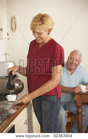 Home Help Sharing Cup Of Tea With Senior Male In Kitchen