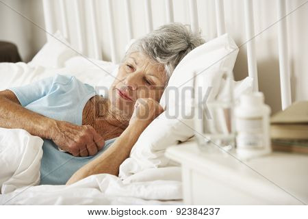 Medication On Bedside Table Of Sleepless Senior Woman