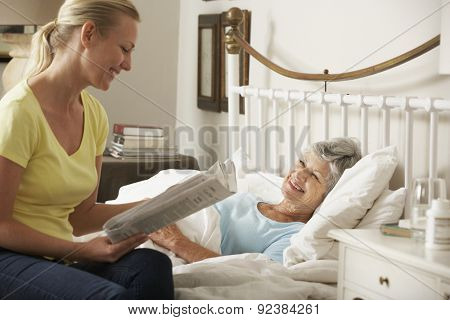 Adult Daughter Reading Newspaper To Senior Female Parent In Bed At Home
