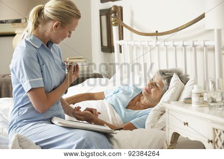 Nurse Taking Pulse Of Senior Patient Patient In Bed At Home