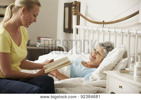 Adult Daughter Reading To Senior Female Parent In Bed At Home