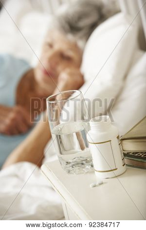 Medication On Bedside Table Of Sleeping Senior Woman