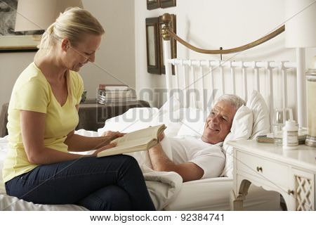 Adult Daughter Reading To Senior Male Parent In Bed At Home