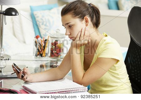 Unhappy Teenage Girl Studying At Desk In Bedroom Looking At Mobile Phone