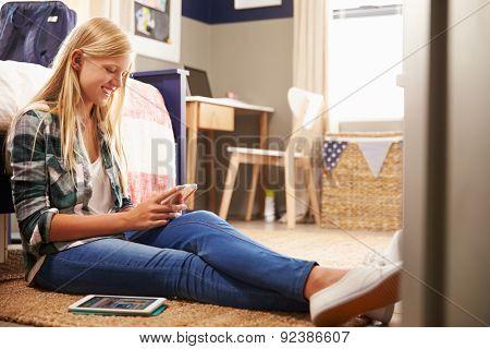 Girl using smart phone in her bedroom