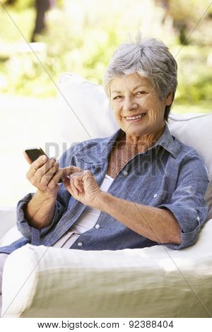 Senior Woman Sending Text Message Sitting On Sofa