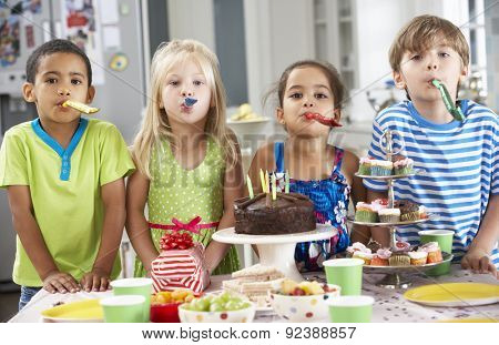 Group Of Children Standing By Table Laid With Birthday Party Food