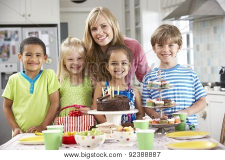 Group Of Children Standing With Mother By Table Laid With Birthday Party Food