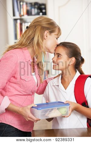 Mother Giving Daughter Healthy Lunchbox In Kitchen