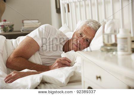 Sick Senior Man In Bed At Home