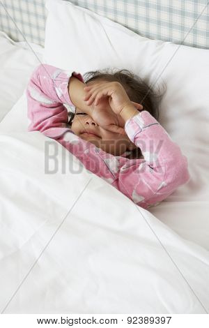 Tired Young Girl Wearing Pajamas In Bed