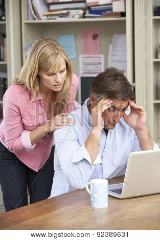 Worried Couple Working In Home Office Together