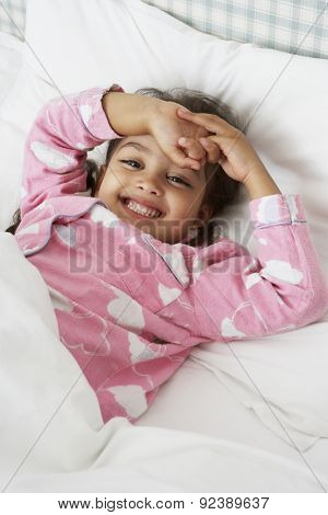 Young Girl Wearing Pajamas Lying In Bed