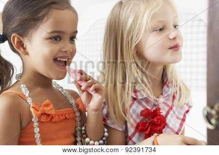Two Young Girls Dressing Up And Putting On Make Up Together