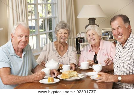 Group Of Senior Couples Enjoying Afternoon Tea Together At Home
