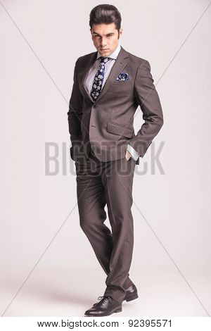 Full body picture of a handsome young business man looking at the camera while holding his hands in pockets.