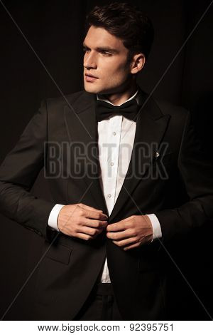 Portrait of a young business man looking away from the camera while closing his jacket.