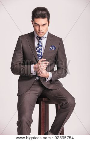Portrait of a business man sitting on a stool holding his hands together.