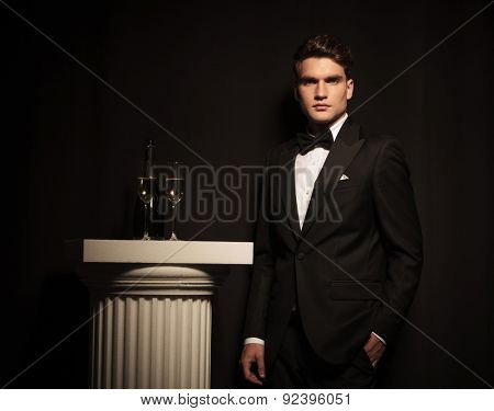 Elegant young business man leaning on a black wall while holding his hand in pocket.