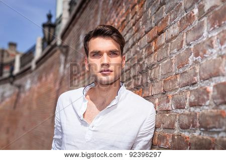 Handsome fashion man leaning on a brick wall while looking away from the camera.