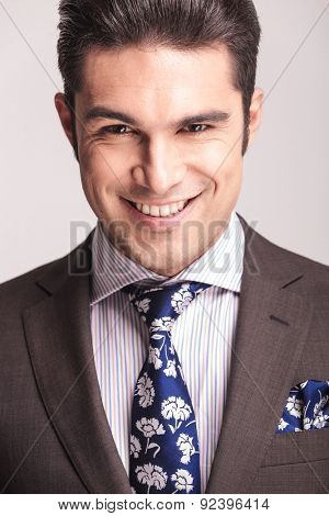 Close up picture of a handsome young elegant business man smiling to the camera.