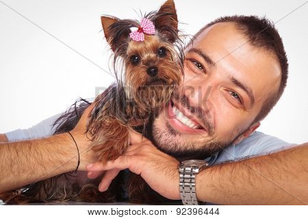 young man is holding his pet yorkshire terrier puppy dog and smiles to the camera