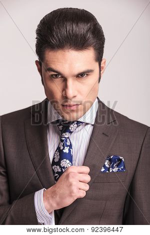 Close up picture of a young handsome business man looking at the camera while fixing his collar.