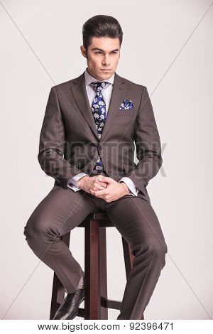 Handsome young business man sitting on a stool while holding his hands together.