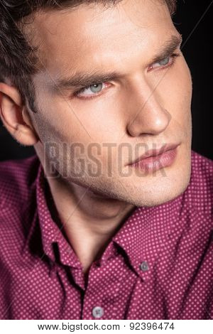Close up of a young handsome man looking away from the camera, thinking.