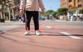 stock photo of leggins  - Closeup of little girl legs with sneakers and black leggins standing over a city runway on a sunny day - JPG