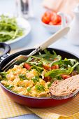 stock photo of scrambled eggs  - Scrambled eggs with fresh tomato and arugula salad in frying pan selective focus - JPG