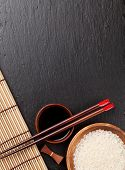 picture of soy sauce  - Japanese sushi chopsticks over soy sauce bowl and rice on black stone background - JPG