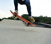 stock photo of skateboard  - closeup of skateboarder legs skateboarding at skatepark - JPG