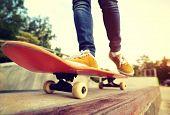 image of skateboard  - skateboarding legs riding on skateboard at skatepark - JPG