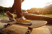 picture of skateboard  - skateboarding legs riding on skateboard at skatepark - JPG