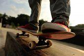 stock photo of skateboard  - closeup of skateboarder legs skateboarding at sunrise skatepark - JPG