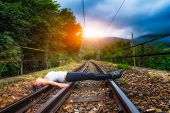 pic of train track  - Girl lying on train tracks in the mountain - JPG