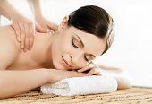 Young and healthy woman in spa salon. Traditional Swedish massage therapy and beauty treatments.  poster