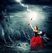 stock photo of lightning  - halloween witch making magic and controls the weather - JPG