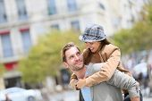 stock photo of piggyback ride  - Young man giving piggyback ride to girlfriend in town - JPG