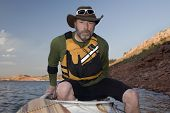 picture of horsetooth reservoir  - mature male boarding his canoe on a mountain lake with red sandstone cliffs  - JPG