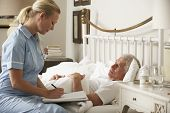 stock photo of visitation  - Nurse Visiting Senior Male Patient In Bed At Home - JPG
