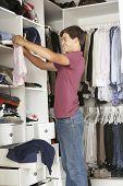 picture of wardrobe  - Teenage Boy Choosing Clothes From Wardrobe In Bedroom - JPG