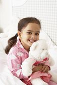 image of pajamas  - Young Girl Wearing Pajamas In Bed With Cuddly Toy - JPG