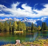 stock photo of snow capped mountains  - City park in the Alpine resort of Chamonix at sunset - JPG